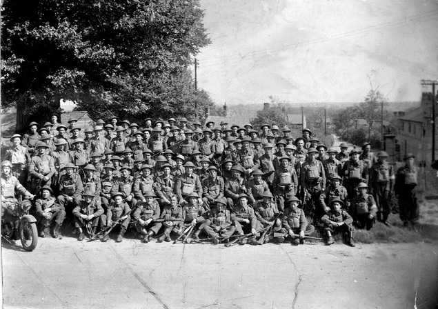 An image showing British troops, pictured in Yardley Gobion in 1913. All are wearing full military uniform, and some can be seen holding their guns, ready at hand.